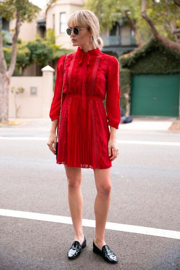 Street style look com vestido curto manga longa vermelho, sapato boyish flat preto, óculos redondo e bolsa com alça corrente.
