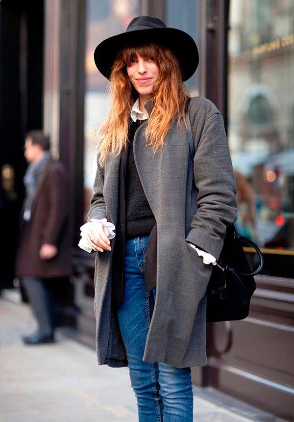 Lou Doillon usa chapéu preto, camisa branca, tricot preto, casaco cinza, calça jeans skinny e bolsa preta
