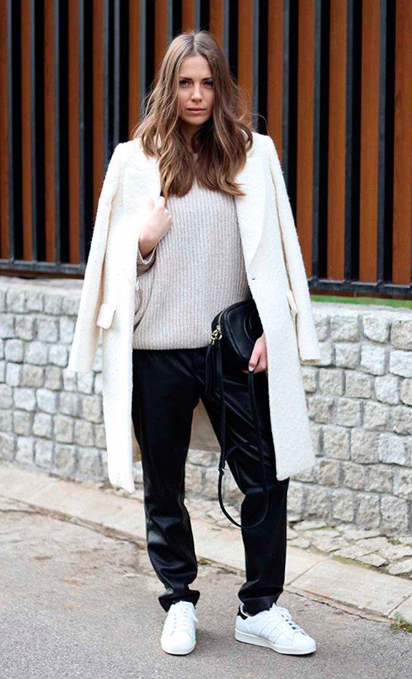 Vanja Milicevic veste maxi tricot nude, casaco sobretudo off white, calça de couro preta e tênis adidas stan smith