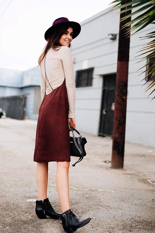 Foto de street style de como usar slip dress com blusa de manga comprida nude, botas pretas e chapéu vinho