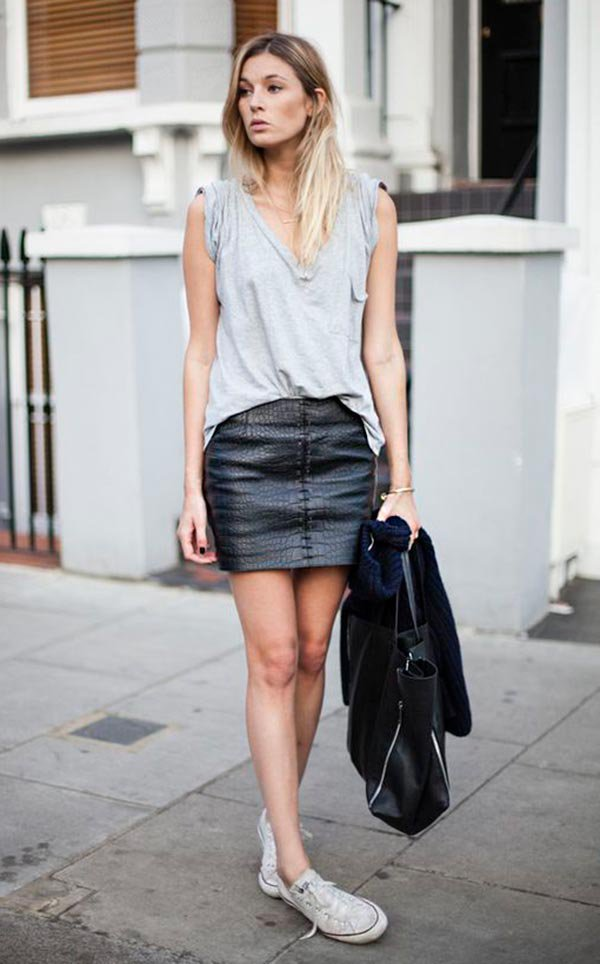 Street style look com blusa cinza, saia couro e tênis converse.