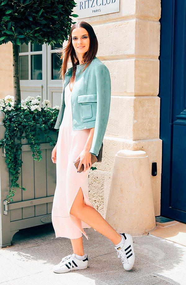 Street style look vestido midi, jaqueta azul e tênis branco.