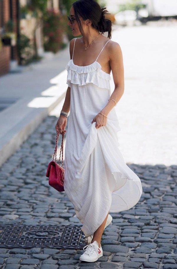 Street style look com vestido comprido branco e tênis.