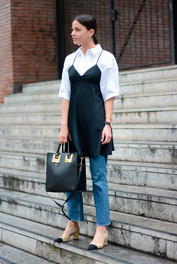 Zina Charkoplia usa camisa branca com slip dress preto sobre calça jeans e sapato bicolor