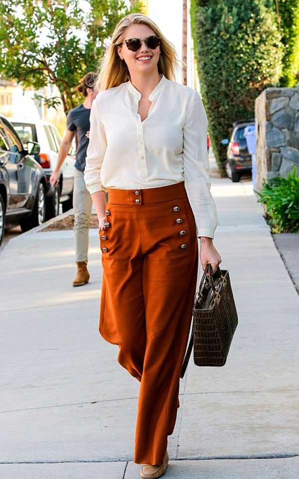Kate Upton investe em camisa off white com calça pantalona e mocassim