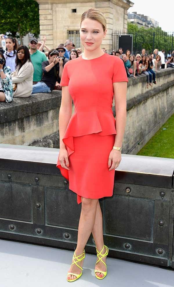 Lea Seydoux usa vestido monocromático laranja com sandália amarela