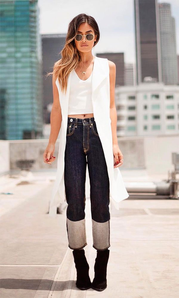 Street style look com colete branco, calça jeans e bota