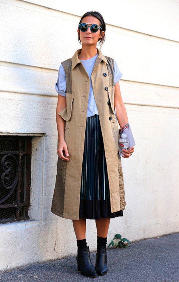Street style look com colete militar e saia plissada.