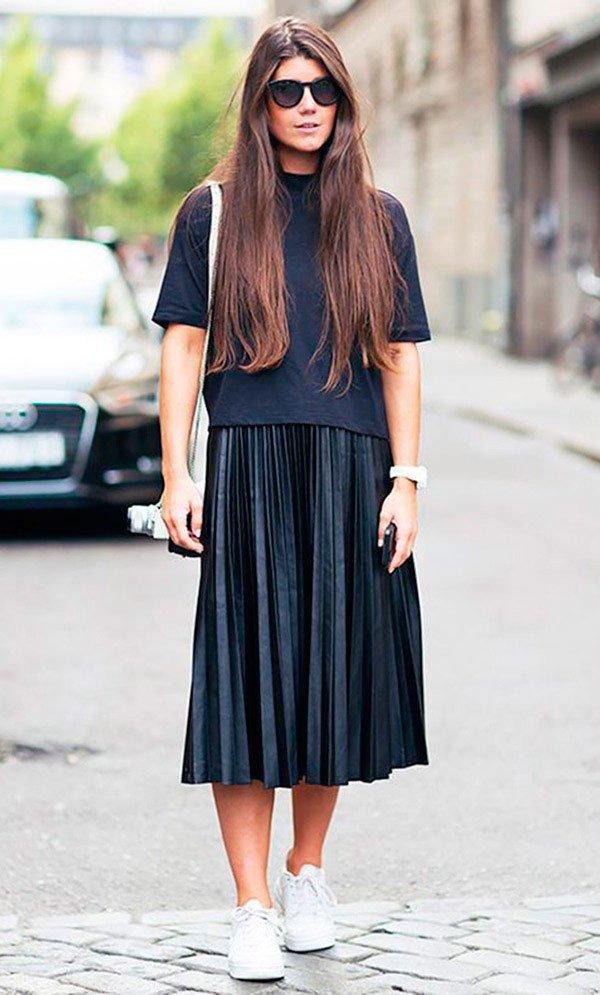 Street style look com blusa ampla, saia plissada midi e tênis.
