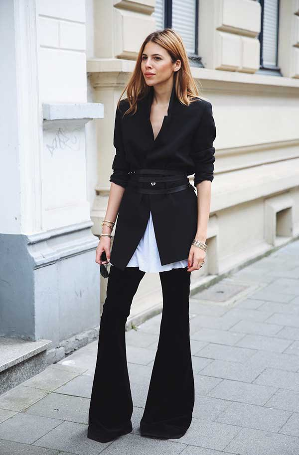 Maja Wyh usa calça flare com camisa branca e blazer preto com sobreposição de cinto