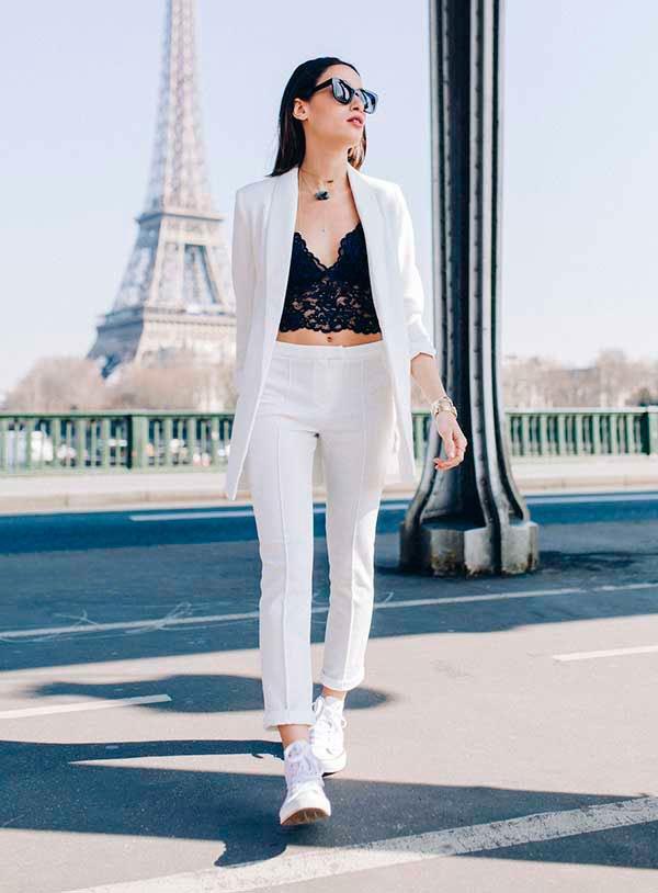 Look de conjunto de calça e blazer de alfaiataria brancos com top de renda e tênis branco