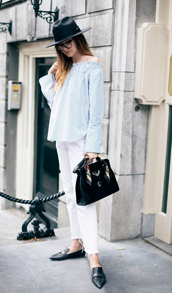 Street style look com blusa ombro a ombro e calça branca.
