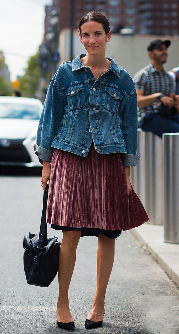 Street style look com saia plissada e jaqueta jeans.