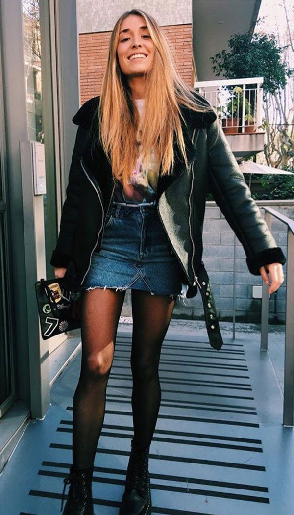 Street style look com jaqueta saia e botas.
